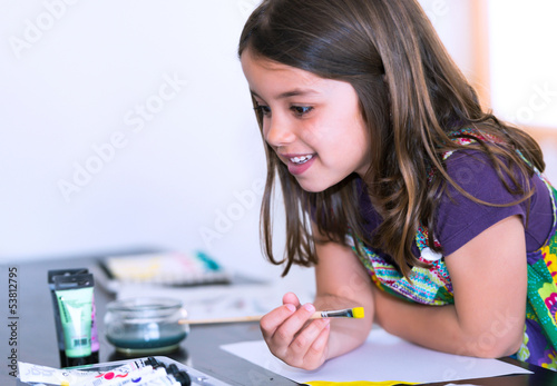 Portrait of a lovely smiling girl painting a picture