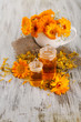 Medicine bottles and calendula flowers on wooden background