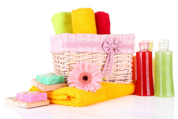 Colorful towels in basket, cosmetics bottles and soap, isolated