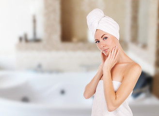 Woman with towel in bathroom with jacuzzi