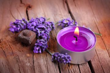 Lavendel und Duftkerze auf rustikalem Holzuntergrund