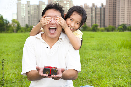 surprised father holding gift box from little girl for father's