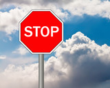 Stop sign on blue cloudy sky background.
