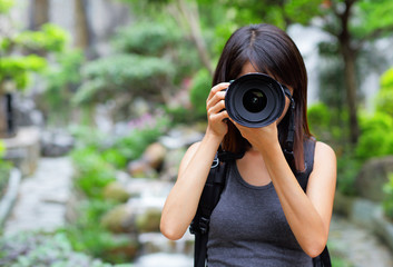 Asian woman taking photo with backpack