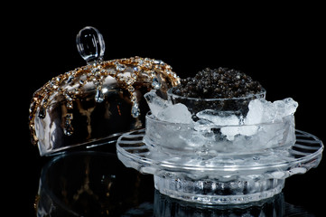Black caviar in ice on a black isolated studio photo