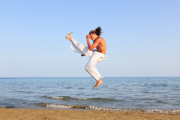 Young adult man  practicing a Kata on the beach