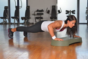 Young woman doing fitness exercises on stepper