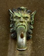A Grungy Ornamental Street Faucet Shaped Like A Lion's Head