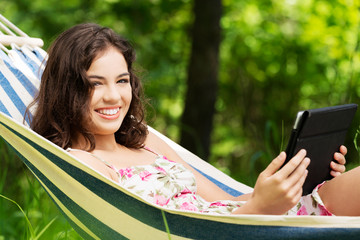 Young woman lying in a hammock in garden with E-Book.