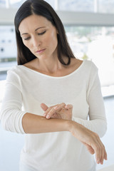 Woman applying ointment on her arm