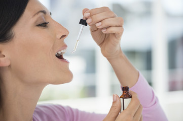 Close-up of a woman taking homeopathic medicine