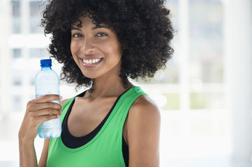 Smiling woman drinking water from a bottle