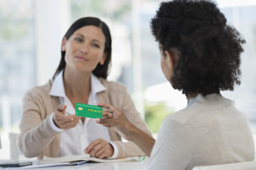Female patient giving health insurance card to a doctor