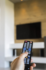Person's hand operating a TV remote control