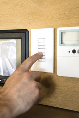 Person pressing switch of a security camera control panel