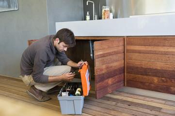 Man repairing a kitchen sink
