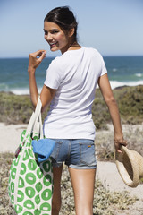 Happy woman carrying a bag on the beach