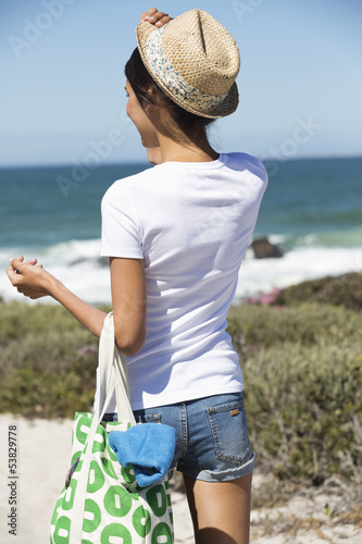 Beautiful woman carrying a bag on the beach