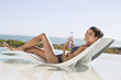 Beautiful woman holding a water bottle while sunbathing on the beach