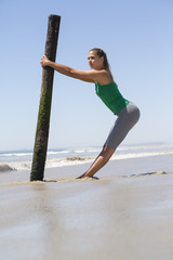 Woman exercising with a wooden post on the beach
