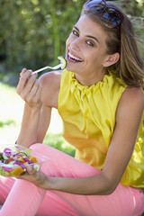 Portrait of a smiling woman eating salad
