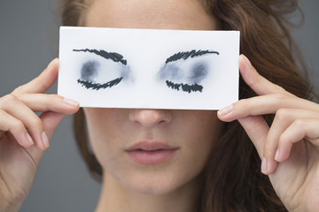 Woman holding a paper with false eyes in front of her face