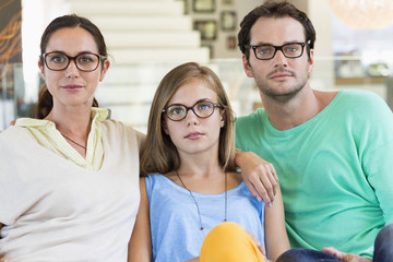 Portrait of a family sitting on a couch and wearing eyeglasses