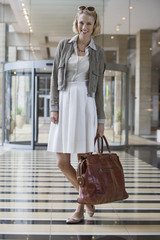 Woman standing on an airport holding a leather handbag