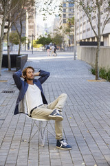 Man relaxing on a chair on a street