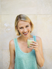 Smiling woman drinking detox