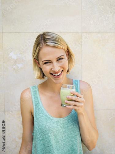Smiling woman drinking detox