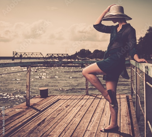 Stylish woman in white hat standing on wooden pier