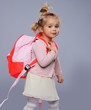 Funny little school girl with a backpack