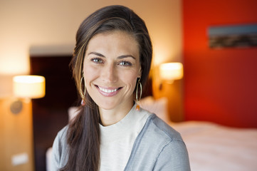 Portrait of a woman smiling in a hotel room