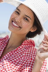 Beautiful woman wearing a hat on the beach