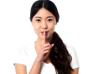 Beautiful asian girl gesturing silence
