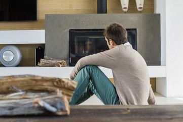 Man sitting in front of a fireplace at home