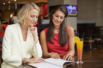 Two female friends looking at menu in a restaurant