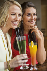 Two female friends enjoying drinks in a restaurant