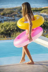 Woman standing with inflatable rings at the poolside