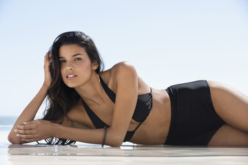 Beautiful woman in bikini lying on the beach