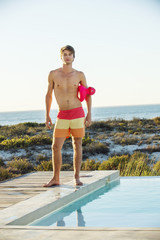 Man standing at the poolside on the beach