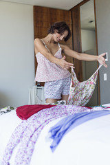 Woman choosing dress at home