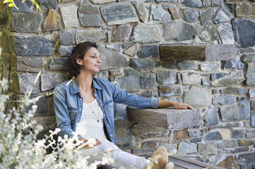 Woman leaning against a stone wall and day dreaming