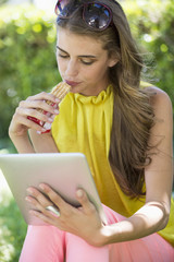 Woman eating chocolate and looking at a digital tablet