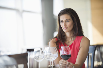 Woman holding a wine glass and thinking in a restaurant