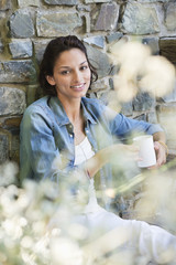 Portrait of a smiling woman leaning against a wall and drinking coffee