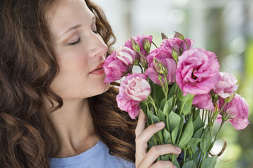 Close-up of a woman smelling flowers
