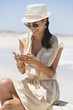 Beautiful woman text messaging on a cell phone on the beach