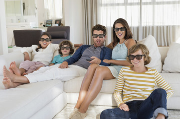 Family watching television at home while wearing 3D glasses